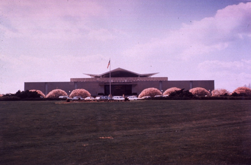 <p>Exterior view of the hyperbolic paraboloid form: front entrance with flag raised, parked cars and trees in bloom.</p>