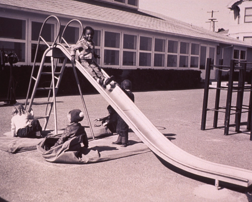 <p>Children playing outside.  An African Amercian child is sliding down a slide while other children are on mats around the slide.</p>