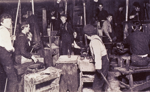 <p>Interior view: several young men and boys are working at various tasks in a glass factory.</p>