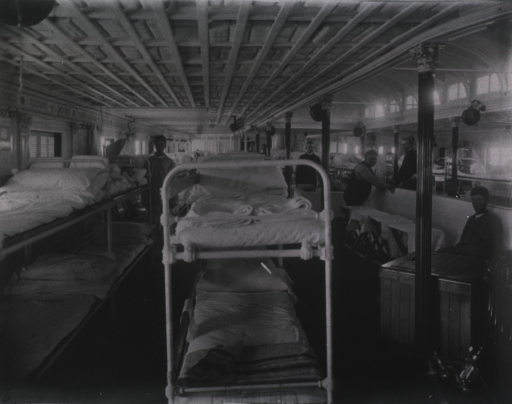 <p>Interior view of Ward 1 showing bunks and several staff and patients.</p>