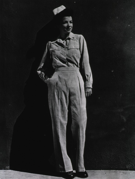 <p>A servicewoman stands against a wall outdoors and poses full-face as she models the suit.</p>