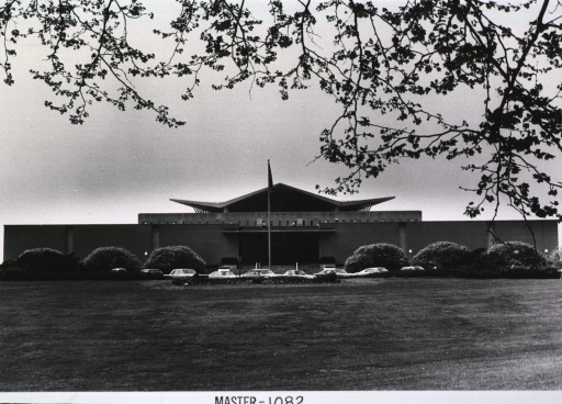 <p>Exterior view of the hyperbolic paraboloid form: front view with flag, parked cars, and trees.</p>