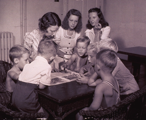 <p>A nursery school instructor is reading to a group of children.</p>