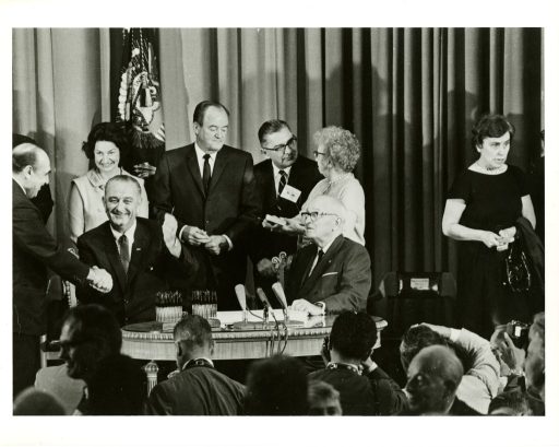 <p>President Lyndon Johnson signs the 1965 Medicare Bill at an Independence, Missouri ceremony.  Standing behind him are Lady Bird Johnson, and Vice President Hubert Humphrey. Sitting next to him is President Harry Truman. Bess Truman is speaking with Congressman Wilbur Mills. President Johnson Shakes hands with Secretary of Health, Education, and Welfare (HEW) Anthony Celebrezze.</p>