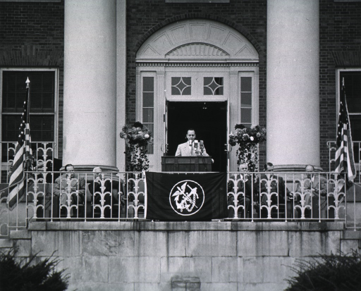 <p>Showing podium area and front of Building 1.  Left to right are: Leonard Scheele, Rolla Dyer, Norman Topping (standing at podium), Oscar Ewing, unidentified person, and William Sebrell.</p>