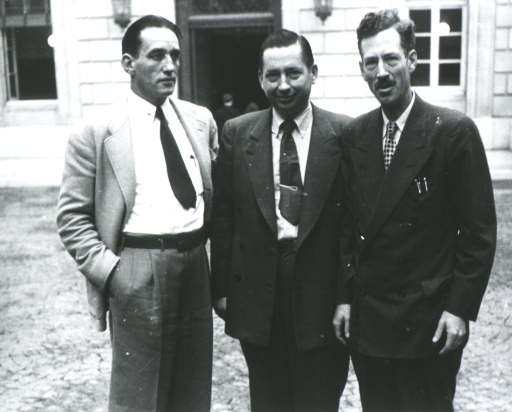 <p>Standing, three-quarter length, full face; with two unidentified men; building in background.</p>