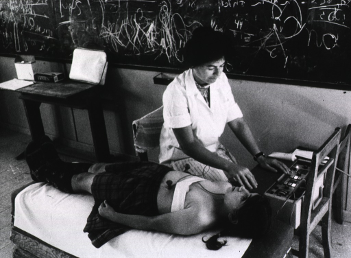 <p>A young girl is connected to a portable electronic device that monitors her heart. The girl is lying on her back, the machine is on a chair, and the technician is sitting in front of it; they appear to be set-up in a classroom.</p>