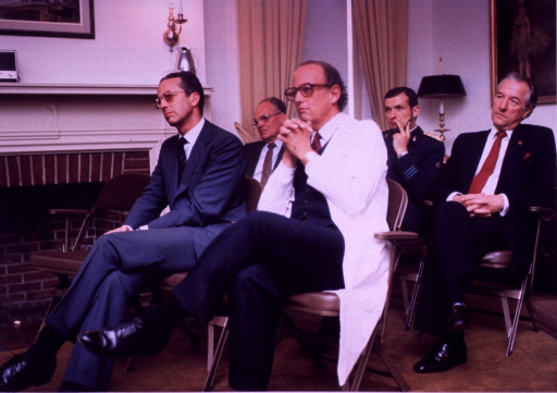 <p>King Baudouin and Donald S. Fredrickson, director of the National Institutes of Health (NIH), are sitting in folding chairs in front of a fireplace in the Stone House.  There is a row of men behind them.</p>