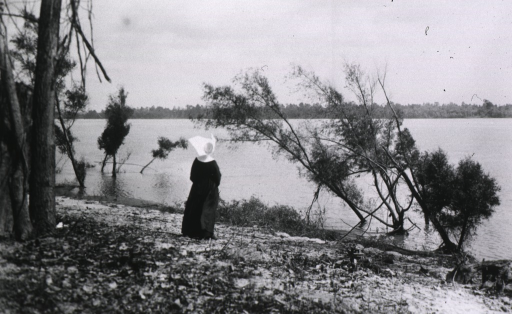 <p>A nun stands on the bank of the Mississippi River, looking out across the river.</p>