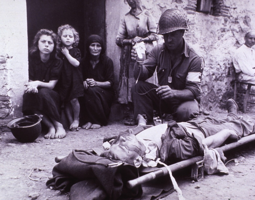 <p>The photograph shows a wounded soldier lying in a street in Sicily during World War II, receiving blood plasma.  There are civilians watching.</p>