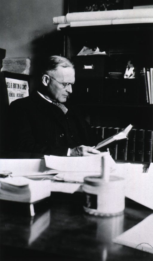 <p>Seated at desk in laboratory.</p>