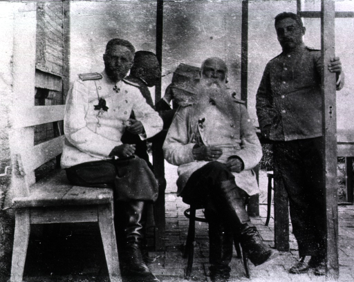 <p>Lieutenant General Kukle, Andrea, Tolstoi, and an unidentified man sit on the porch, one reading the paper and smoking.</p>