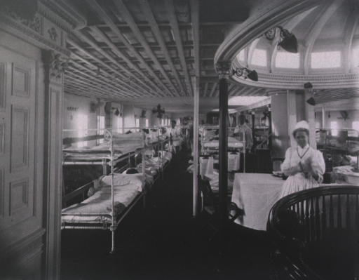 <p>Interior view of Ward 3 showing bunks, patients, staff, and a nurse.</p>
