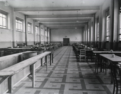 <p>Rows of tables are shown in an unoccupied, high-ceilinged hall.</p>