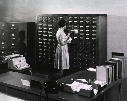 <p>Interior view: File cabinets, a card catalog, a typewriter, and on top of a desk is a telephone and reference books.</p>