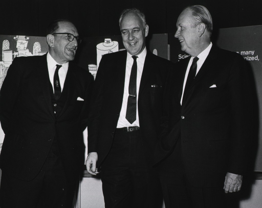 <p>Three men stand together in front of an exhibit display.</p>