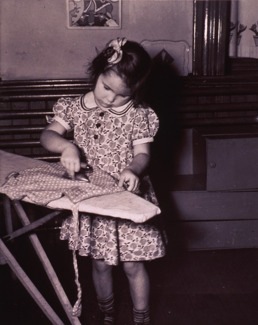 <p>A young girl is ironing.</p>
