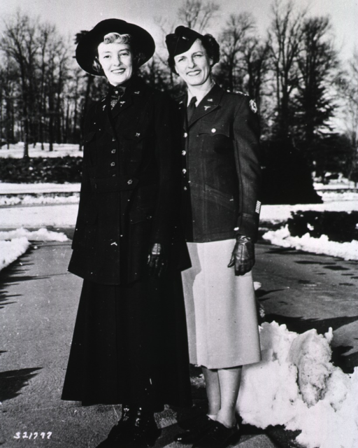 <p>The two servicewomen stand side-by-side outdoors on a snow-plowed drive.  They pose full-face as they model the clothing.</p>