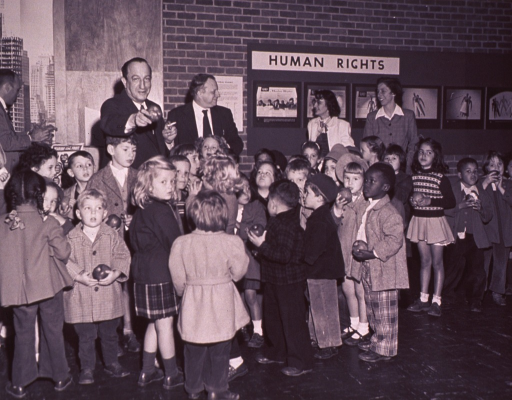 <p>A man is holding an apple in one hand and a cigarette in the other.  Children are in front of him holding apples.</p>