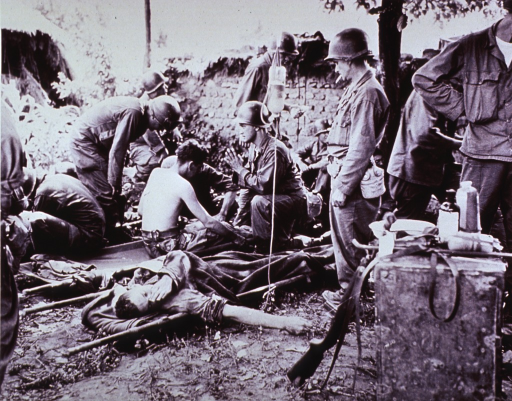<p>Showing wounded American soldiers receiving first aid (blood plasma) at a field clearing station in Korea.</p>