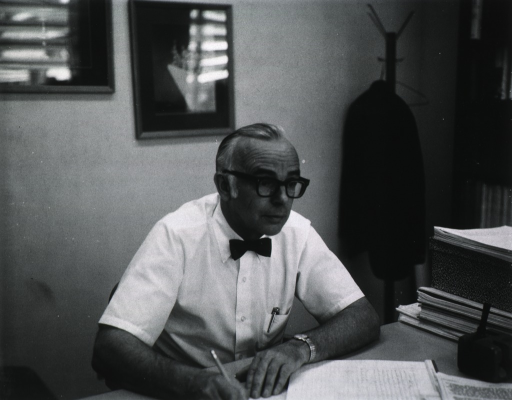 <p>Half-length, turned slightly to right, wearing glasses, seated at desk, writing.</p>
