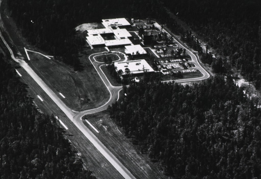 <p>Aerial view of several buildings in a wooded area.</p>