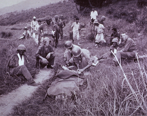 <p>Photograph of medic giving first aid in Korea, 1950.</p>