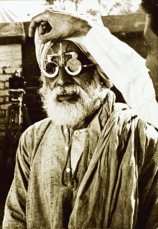 <p>A old man is being tested for new lenses using an apparatus by which different lenses can be inserted and a proper selection made.</p>