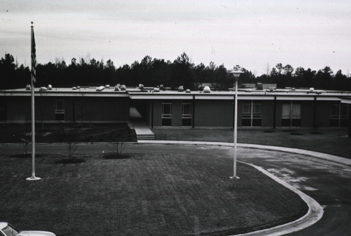 <p>Exterior view showing flag pole, circular drive, and the front of a building.</p>