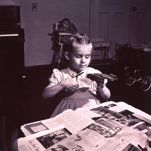 <p>A young girl is cutting pictures from magazines.</p>
