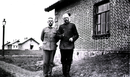 <p>Chief Medical Inspector Garbatsumtch and another officer stand outside a building (hospital?).</p>