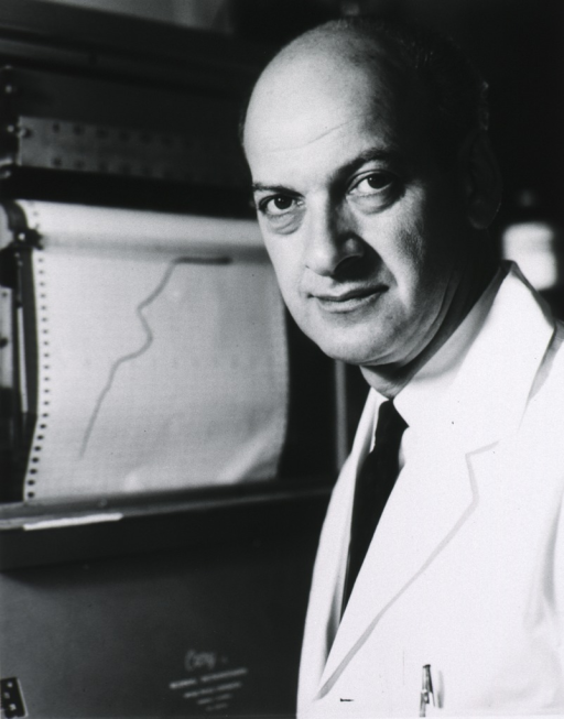 <p>Head and shoulders, left pose, full face; wearing white lab coat; graph in background.</p>