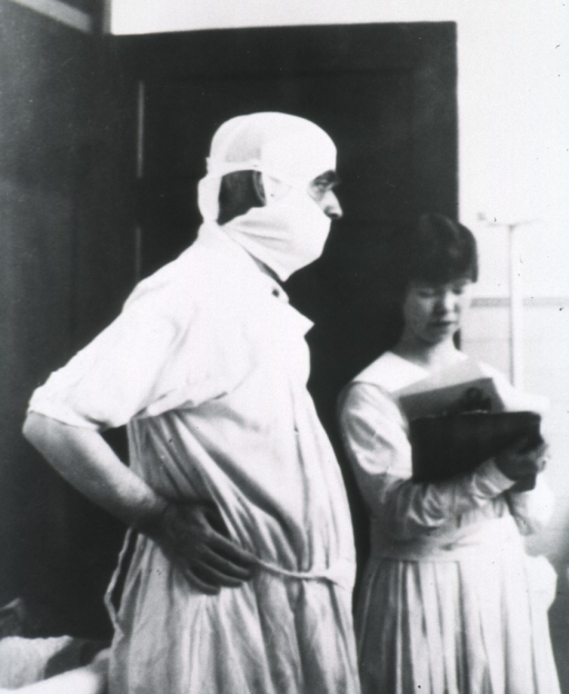 <p>Three quarter length, right profile; standing in surgical gown, mask and cap with assistant.</p>