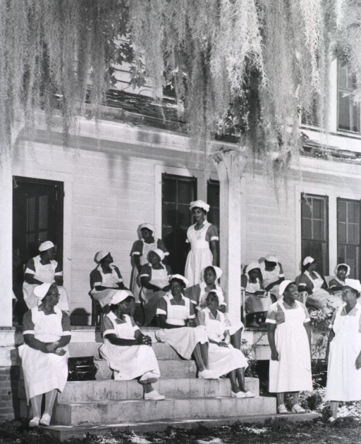 <p>Exterior view showing a group of African American students sitting on steps waiting for the lunch bell to ring.</p>