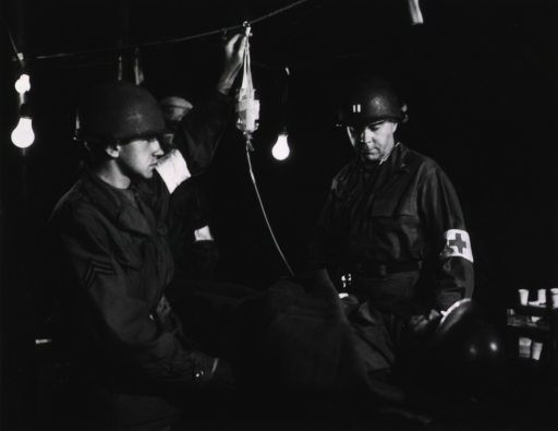 <p>Three servicemen tend to a wounded serviceman who is supine on a hospital bed.  One of the servicemen adjusts a glass IV containing a fluid that appears to be a blood product, perhaps plasma.  Several light bulbs illuminate the scene.</p>