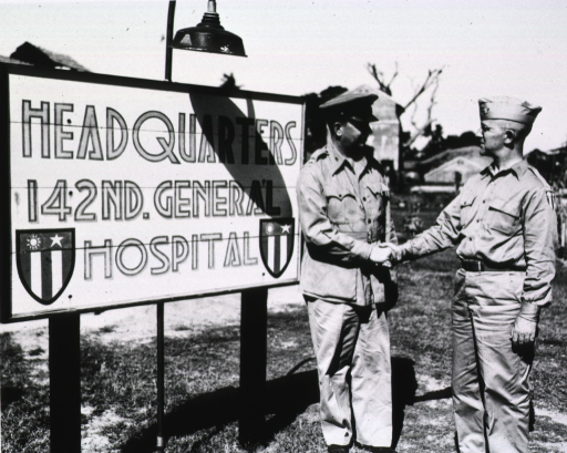<p>The two men shake hands in front of the hospital sign that is placed on posts in front of the hospital.</p>