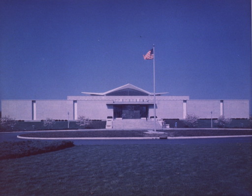 <p>Exterior view of the hyperbolic paraboloid form: front entrance; people are standing in front of the NLM sign, the bottom of the steps, and on the sidewalk.</p>