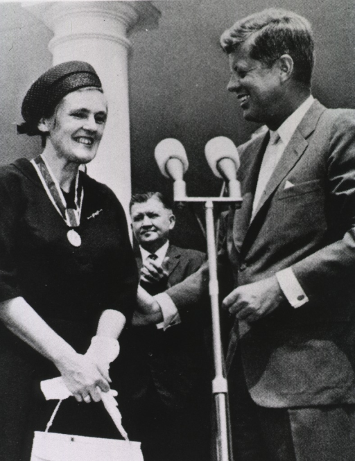 <p>Dr. Kelsey and President Kennedy are shown three-quarter length, standing at a microphone during the awards ceremony at which she received the Gold Medal for Distinguished Federal Civilian Service.</p>