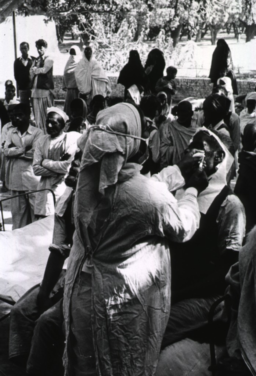 <p>Exterior view: at an outdoor clinic a nurse is giving a patient an injection. Many people are gathered, observing what may be mass cataract operations (not shown).</p>