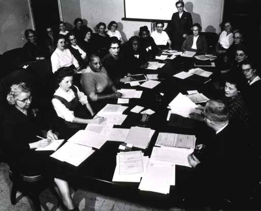 <p>This picture shows P.H.N.'s, nutritionists, nurse midwives, head group leaders of the institute and mental health consultants reviewing lesson plans, schedule of activities, the midwife certificate of registration, and birth certificate.</p>