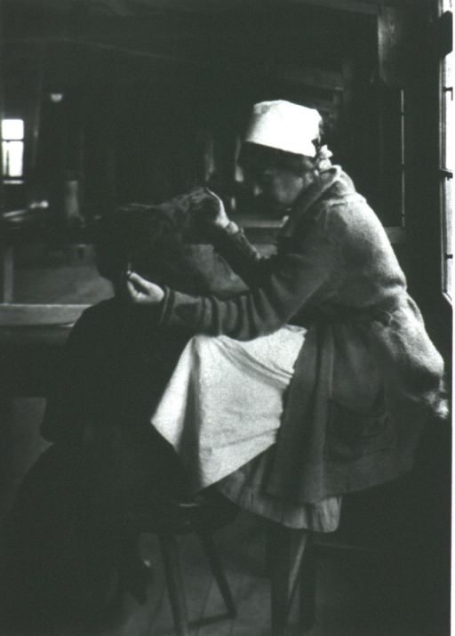 <p>A nurse sitting on a high stool inspects the hair of a woman sitting on a foot stool.</p>