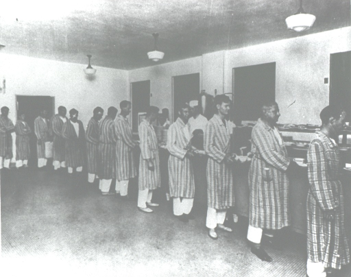 <p>A line of patients wearing hospital bathrobes and pajamas wait in the hospital cafeteria at meal time.</p>