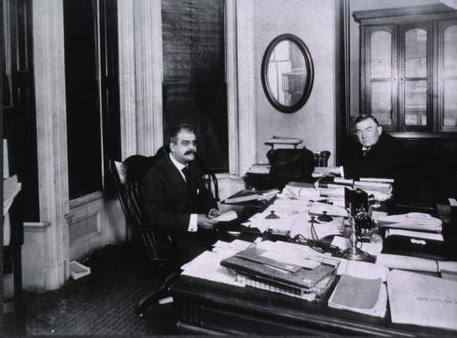 <p>Three-quarter length, seated at desk; in conference with W.S. Larner.</p>