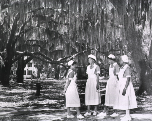 <p>Group of four African American midwife students getting to know each other on the grounds of the Institute.</p>