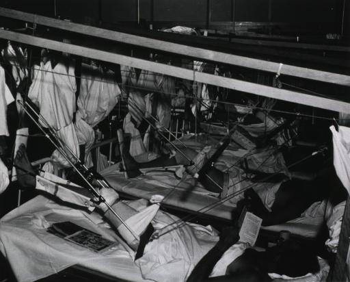 <p>A group of wounded soldiers is shown lying on hospital beds, their legs raised in slings.</p>