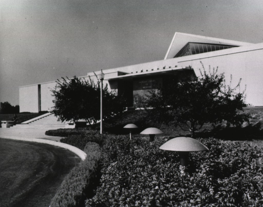 <p>Exterior view: front entrance as seen through trees, bushes, and plants; ground lights are among the ground covering.</p>