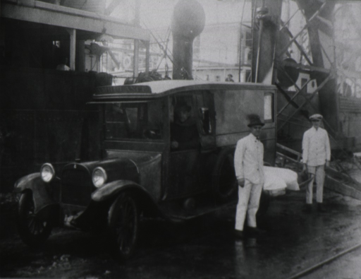<p>Ambulance parked on a dock, ship in the background; driver sitting behind the wheel, and two attendants standing next to the vehicle.</p>