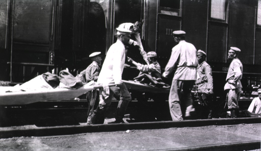 <p>Several soldiers(?) lift typhoid patients lying on strechers onto a hospital train.</p>