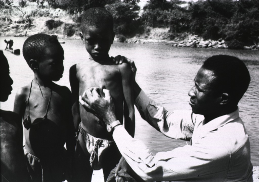 <p>Exterior view, at the edge of a river: a physician is examining a lump on the chest of a young boy; two other boys are standing nearby.</p>