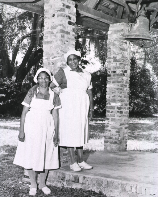 <p>Showing two African American midwife students standing near the bell on the grounds of the Institute.</p>
